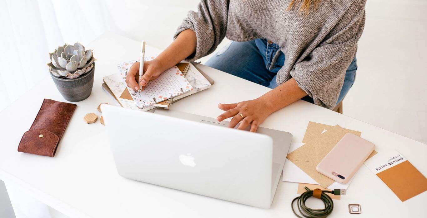 woman sitting at desk planning which wordpress plugins she needs for her business website