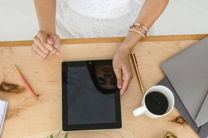 Woman working at desk with a tablet and coffee mug