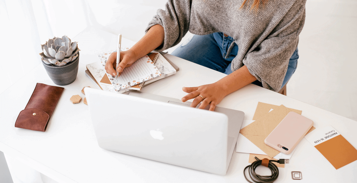 woman taking notes at her desk about how to make sure her website makes a great first impression